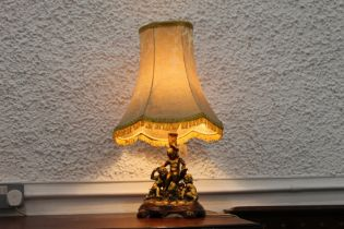 Giltwood effect table lamp and shade with cherub base, height +/-64 cm.