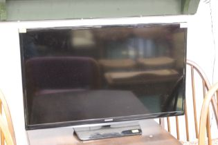 """Samsung flat screen TV set with remote control, 32"""" screen."""