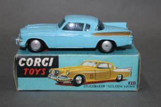 "A Corgi Studebaker ""Golden Hawk"", (211), having a blue body, gold rear wing flashes and flat hubs,"