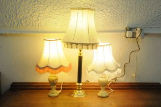 A pair of matching table lamps and shades and a single table lamp and shade