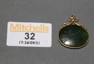 A gilt metal mounted jade oval pendant engraved to front with native figure and to reverse worded