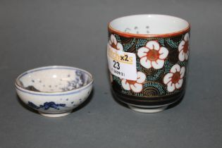A oriental porcelain cylindrical sake cup decorated to exterior with flowers and internally with