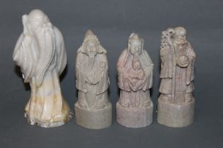 A carved soap stone figure of a standing sage and 3 similar smaller figures