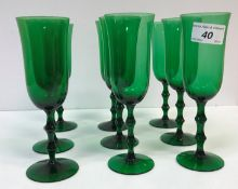 A set of eighteen green glass flutes on double knop stems to circular foot, 18.