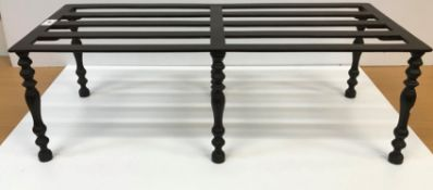 A 19th Century cast iron trivet, the slatted two part top on six baluster turned and ringed legs,