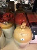A collection of eight stoneware flagons, each with impressed or painted marks,