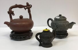 A Chinese Yi Xing teapot with figural decorated handle and script decorated main body,