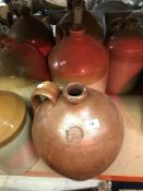 A collection of seven un-marked stoneware flagons and a collection of nine glass demi-johns