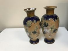 A pair of Doulton Lambeth stoneware vases each decorated with floral spray and stamped to base,