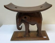 """An African carved hardwood """"elephant"""" stool on rectangular chamfered base, 53 cm wide x 49 cm high"""