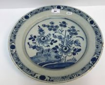 An early 19th Century Dutch Delft charger decorated in the Chinese taste with flowers and fence,