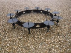 A modern wrought iron hanging ceiling light in the Gothic style with ten pricket candle holders