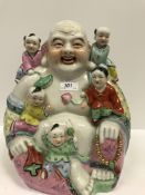 A 20th Century Chinese figure of a seated smiling Buddha with five children, 32.5 cm high