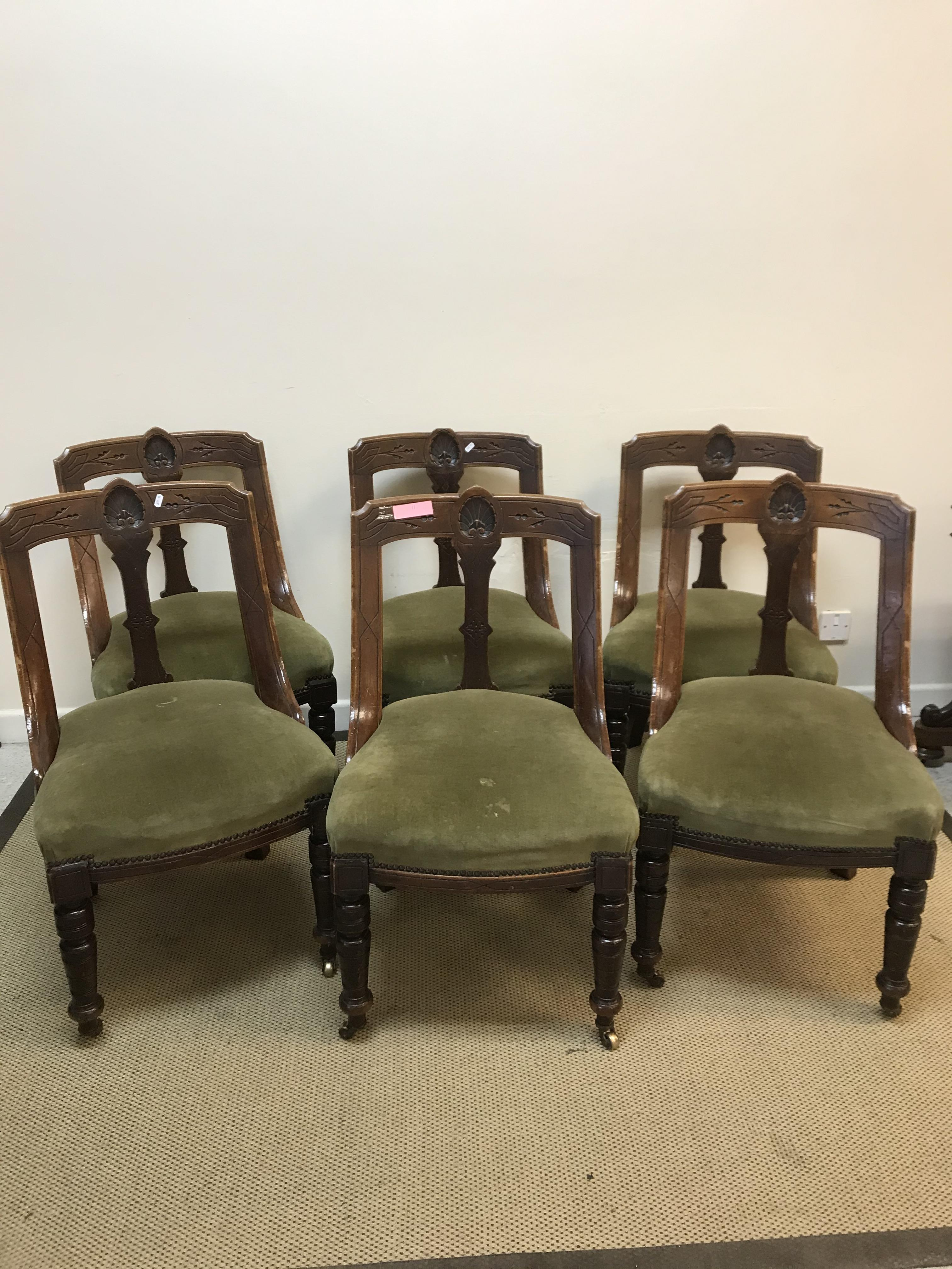 A set of six Victorian carved walnut framed shaped back dining chairs in the Aesthetic taste, raised