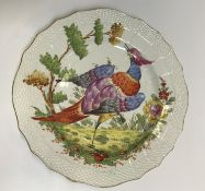 A Chelsea plate, the centre field decorated with an exotic bird in a landscape within a basket