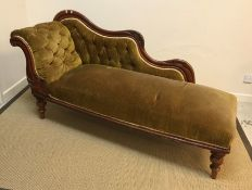 A Victorian mahogany framed buttoned upholstered chaise longue with carved show frame, raised on