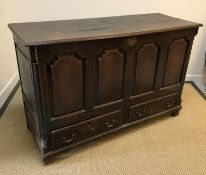 A late 18th Century oak mule chest, the rising top over four fielded arched panels and two drawers