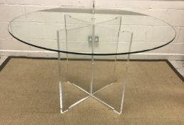 WITHDRAWN A modern circular glass top table on perspex X framed legs