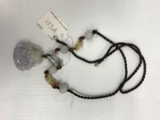 A mauve jade pendant as a seated smiling Buddha, 4.3 cm x 4.1 cm, on silk and jade chain link