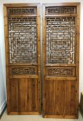 A modern Chinese stained pine and pierced two fold screen with geometric and foliate decoration over