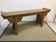 A Chinese elm altar table, the top with scroll ends above a cloud carved frieze on square supports