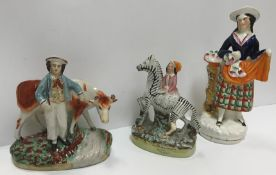 """A collection of thirteen Victorian Staffordshire pottery figures including a pair of Spaniels, """"Girl"""