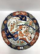 An early 20th Century Japanese Imari charger, the centre field decorated with panels of figures