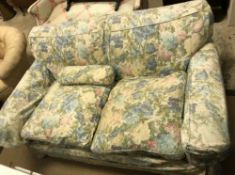 A circa 1900 upholstered two seat sofa with pale floral loose covers, approx 158 cm wide x 90 cm