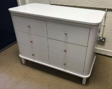 A modern white painted MDF chest of six drawers with brown leather loop handles, flanked by pull-out