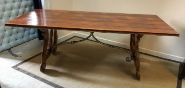 A modern Spanish style walnut dining table, the plank top with moulded edge on shaped end supports
