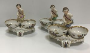 A set of three 19th Century Berlin porcelain twin bowl salts with putti decoration, bearing blue