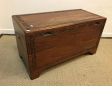 An Eastern camphorwood trunk with foliate carved decoration raised on bracket feet, 100.5 cm wide
