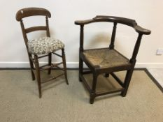 A 19th Century oak yoke-back rush seat corner chair on turned front leg united to the other three