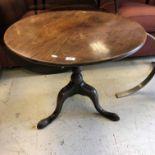A late George III mahogany tea table, the circular top on a turned pedestal to cabriole tripod base,