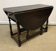 An 18th Century oak oval gate-leg drop-leaf dining table on turned and ringed supports to block feet