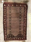 A Turkamen prayer rug, the central panel set with architectural design on an aubergine and cream