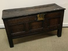 An 18th Century oak coffer, the single piece carved plank top over a three panel front with