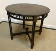 An Edwardian mahogany circular centre table on cluster column supports united by fretwork carved