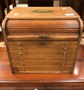 A mahogany table top chest with tambour upper section revealing a tray over six drawers, together
