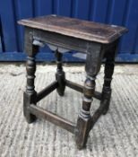 A 17th Century joined oak stool, the single piece top with moulded edge over a carved frieze on