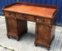 A Victorian mahogany kneehole desk of small proportions, the three quarter galleried top over