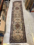 A Persian runner, the central panel set with all-over floral decoration on a cream ground within a