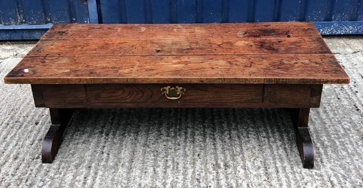 An oak coffee table, the three plank top above a frieze drawer on end pillar supports to splayed