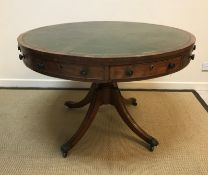 A Victorian Regency style mahogany drum table, the top with tooled and gilded leather insert over