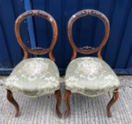 A set of six Victorian walnut balloon back dining chairs with upholstered seats on turned and fluted