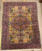 A mid 20th Century Tabriz rug, the central panel set with all-over animal and floral motifs on a