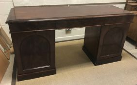A Victorian mahogany sideboard, the plain top with moulded edge above three frieze drawers, raised