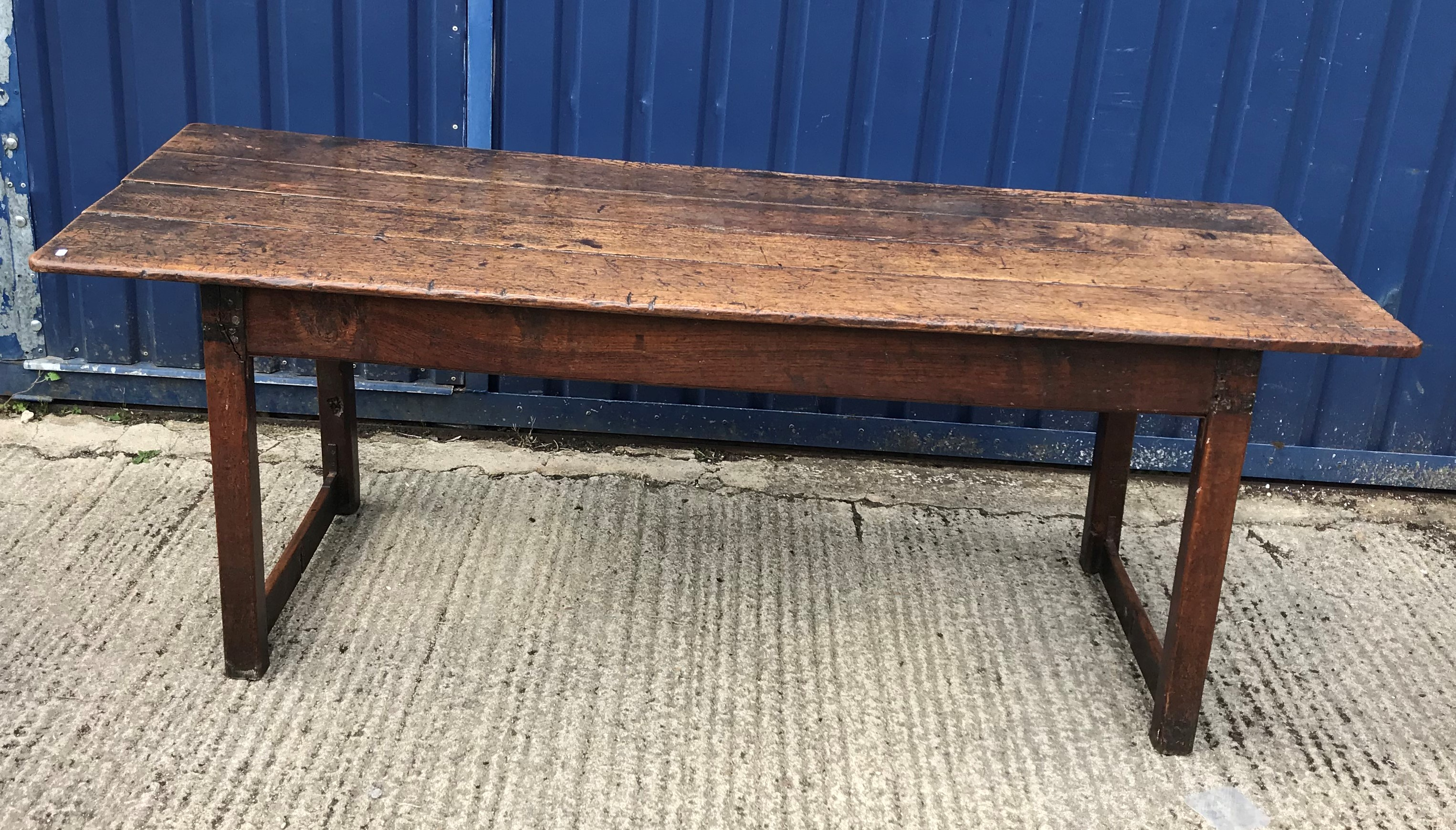 A 19th Century oak refectory style dining table, the four plank top above a plain frieze, raised