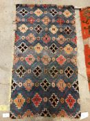 A Caucasian carpet, the central panel set with three repeating medallions on an orange ground,