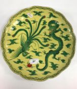 An early 20th Century Japanese Fukagawa famille verte / jaune plate, the main field decorated with a